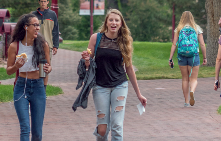 Undergraduate female students walking through summer time campus