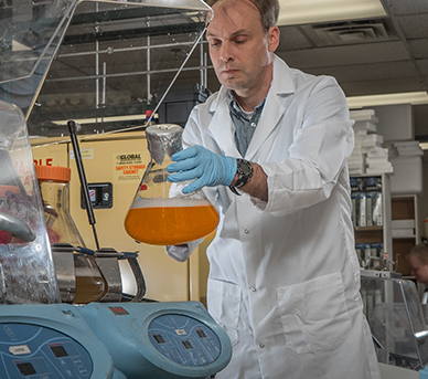 Researcher examines a fluid sample in a lab.