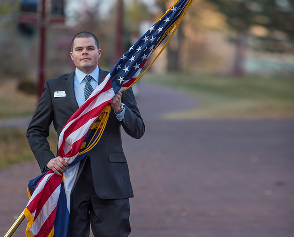 Veteran carrying U.S. flag.