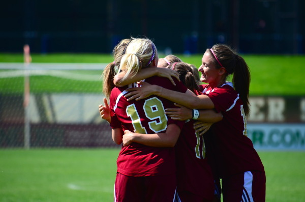DU Women's soccer team hugs after a score