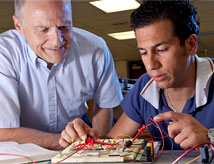 Professor helping student in electronics lab