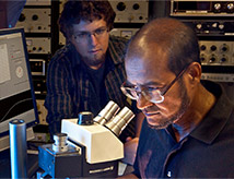 Student and professor looking in microscope