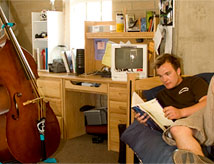 Graduate student studying in his furnished on-campus apartment