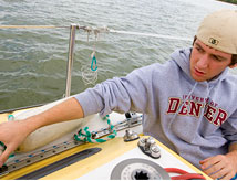 DU student conducting experiments on a boat