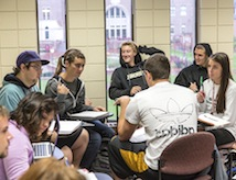 A small class of students gather in a Sturm Hall classroom.