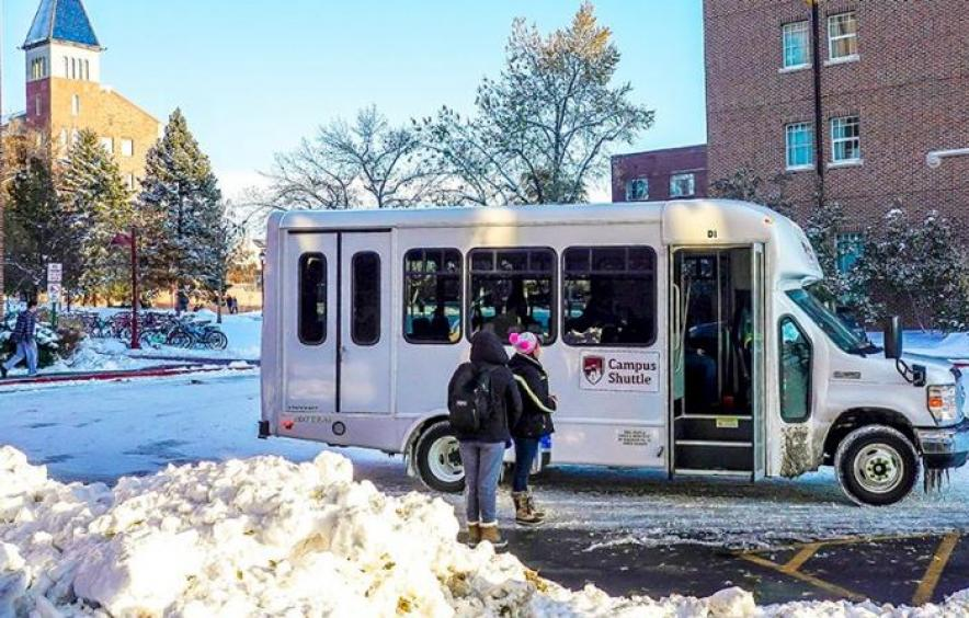 students getting onto the campus shuttle on a snowy morning