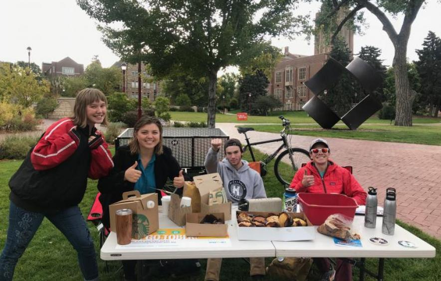 students smiling for the camera as the run the Mobility Munchies table and give away coffee and donuts