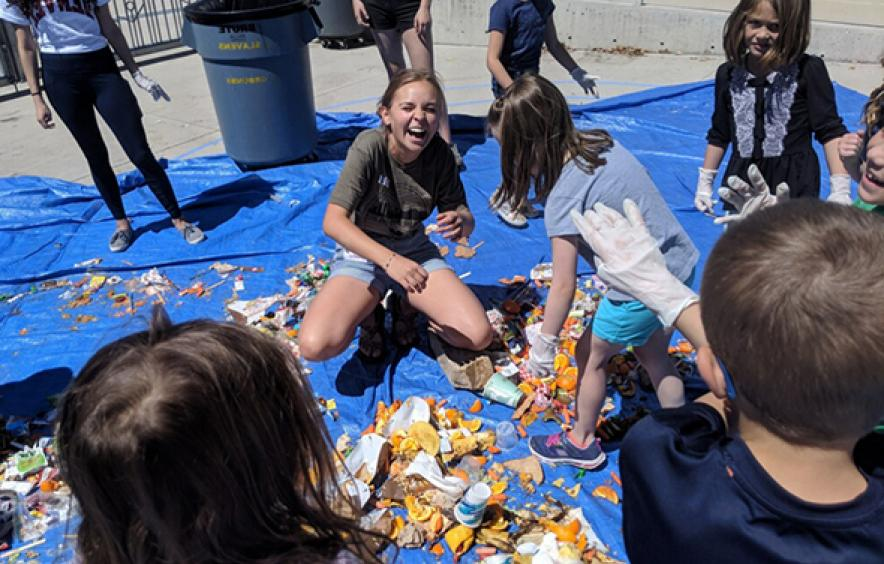 youth going through recyclables laughing