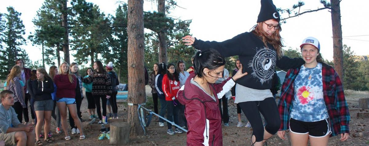 two students helping one student walk tightrope in forrest