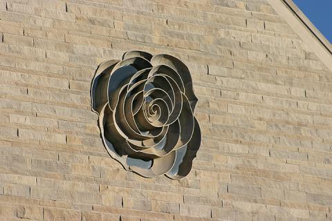 """newman-center-rose """"typeof ="""" foaf: Image """"/></div><p> <span> <span> Las flores, como arte, son comunes en todo el campus de DU. En el lado oeste del Newman Center for the Performing Arts hay un gran rosetón que mira hacia las montañas. Cab Childress, arquitecto universitario cuando se inició la planificación del Centro Newman, había regresado de unas vacaciones en Francia, donde había visitado numerosas catedrales con exquisitos rosetones. Decidió que quería que el edificio incluyera una ventana que representaría la rosa entregada a los artistas al final de un espectáculo. El actual arquitecto universitario Mark Rodgers encontró una rosa en el lado norte del campus que finalmente se utilizó para el diseño de la ventana. </span> </span></p></p><div alt="""