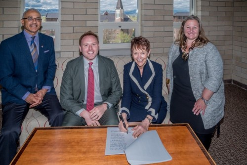 University of Denver Chancellor Rebecca Chopp signs a partnership with Andrew Hermalyn, executive vice president of strategic partnerships for 2U inc. They are joined by Dean Brent Chrite and Dean Amanda Moore McBride.