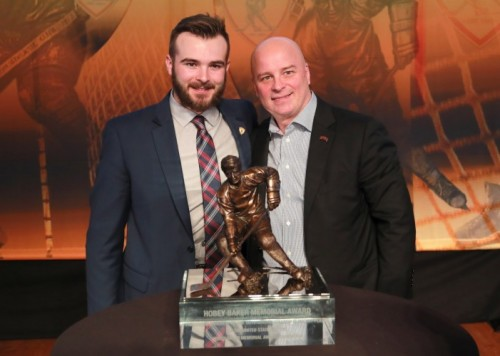 Will Butcher and Coach Jim Montgomery pose together with the Hobey Baker Award.