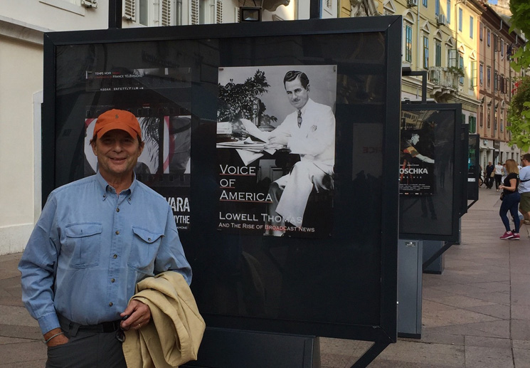 Rick Moulton stands before a poster promoting his new documentary