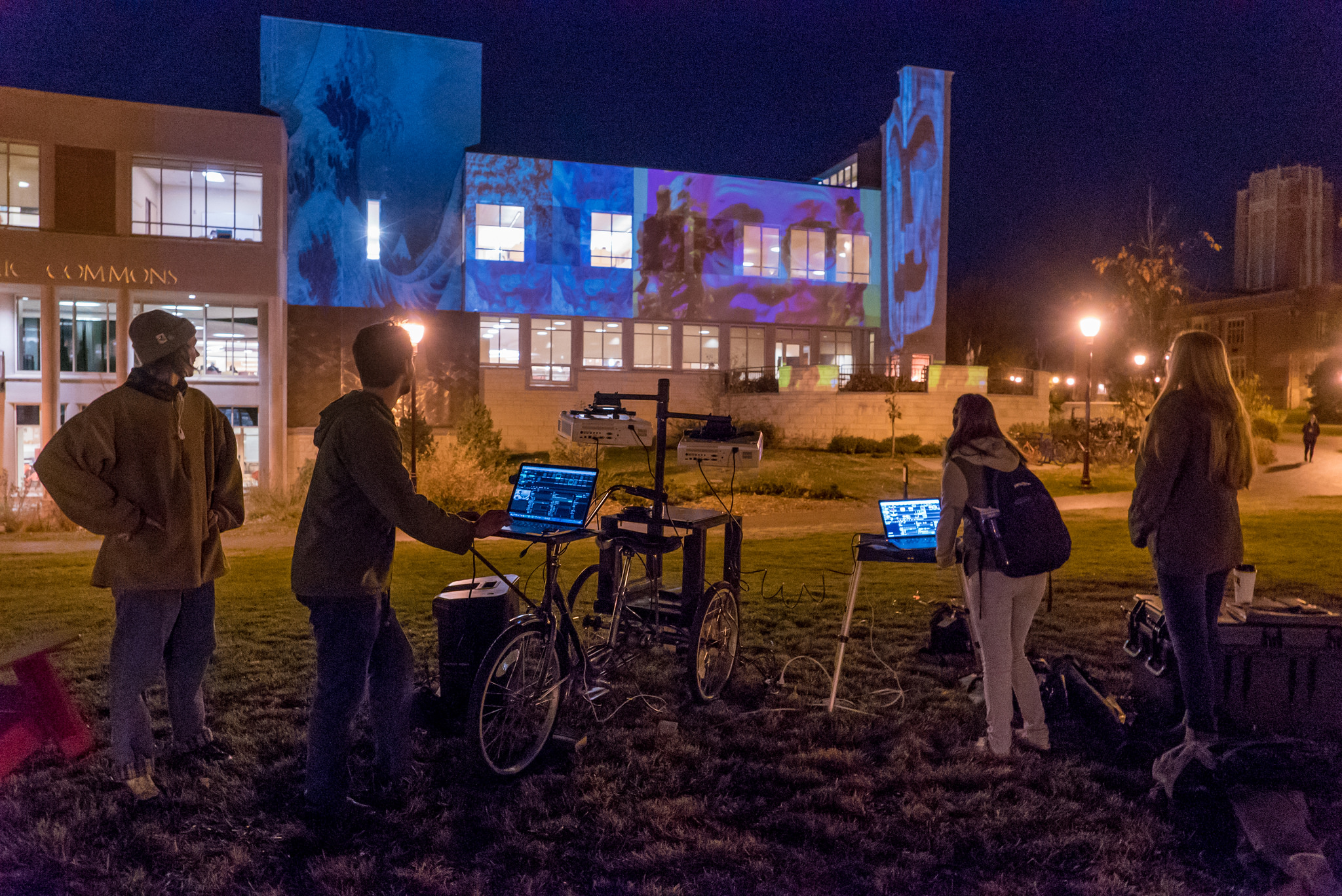 students projecting art on building