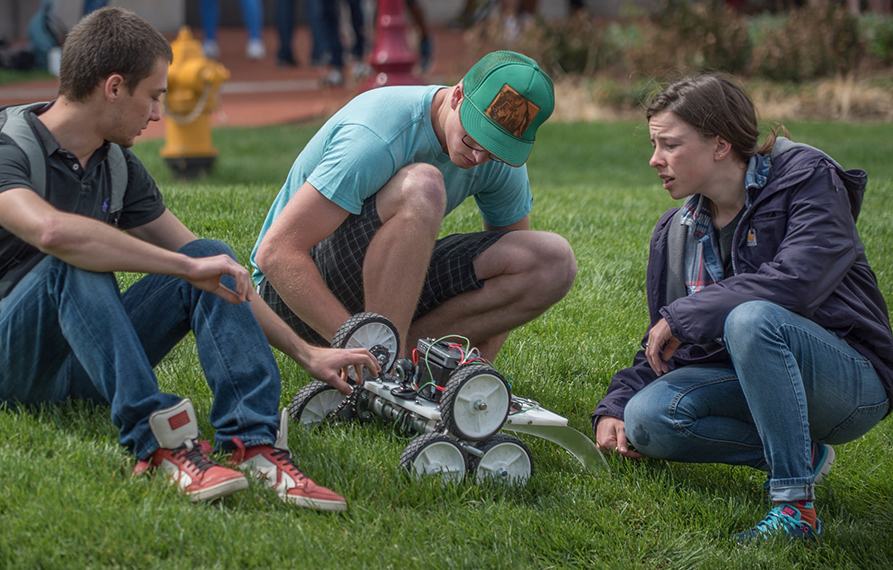 Students gather on the lawn to discuss a robot they're constructing.