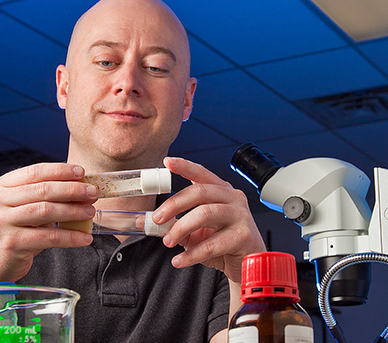 Professor Todd Blankenship examines test tube samples in a research lab.