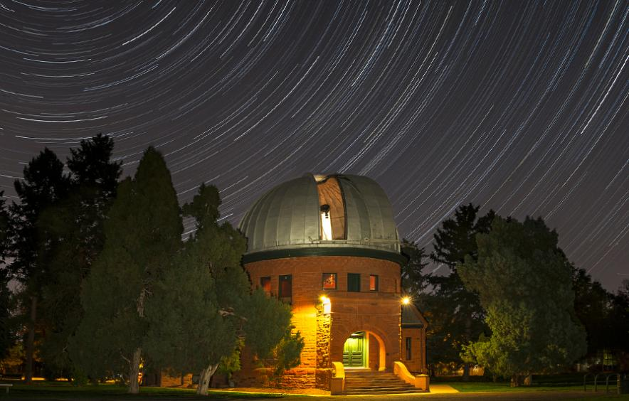 The Chamberlin Observator, an astronomical observatory in Observatory Park against the night sky.